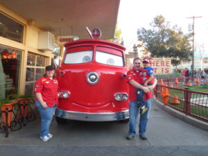 Patrick and his family standing by a red truck