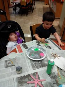 Aliyah sits at the table with her twin brother Ezra