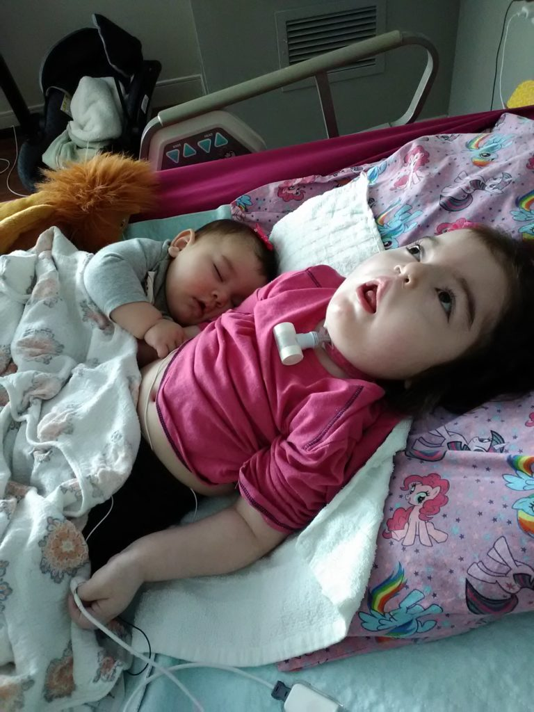 Aliyah cuddling with her baby sister Hanna