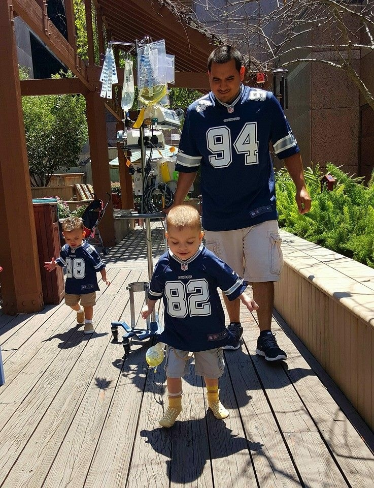 Juan, his dad, and his brother all walking along wearing Dallas Cowboys jerseys